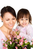 Beautiful woman with a daughter and flowers — Stock Photo