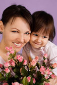 Beautiful female with a daughter and flowers — Stock Photo