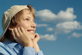 A beautiful caucasian boy in a cap sits — Stock Photo
