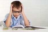 白种人的年轻男子坐在一本商业杂志上和认为 — 图库照片