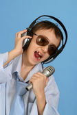 Caucasian handsome young man with headphones and a microphone po — Stock Photo