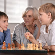 Two boys and grandmother playing chess — Stock Photo