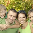 Friendly family in green shirts — Stock Photo #29178459