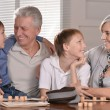 Two boys and grandparents playing lotto — Stock Photo #29178511