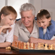 Two boys and grandfather playing chess — Stock Photo #29179125