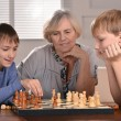 Stock Photo: Two boys and grandmother playing chess