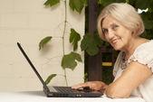Smart older woman sitting on the veranda — Stock Photo