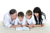 Tre personer läser en bok på — Stockfoto