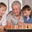 Two boys and grandfather playing chess — Stock Photo #29180745