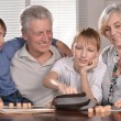 Two boys and grandparents playing lotto — Stock Photo