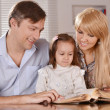 Parents reading a book their daughter  — Stock Photo