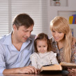 Stock Photo: Parents reading book their daughter