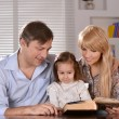 Parents reading a book their daughter — Stock Photo #29181419
