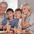 Two boys and grandparents playing lotto — Foto de Stock
