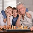 Two boys and grandfather playing chess — Stock Photo #29182941