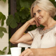 Stock Photo: Pensive older womsitting on veranda
