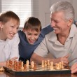 Two boys and grandfather playing chess — Stock Photo #29184747