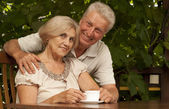 Glorious older couple sitting on the veranda — Stock Photo