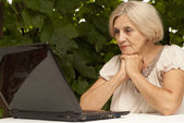 Tops older woman sitting on the veranda — Stock Photo