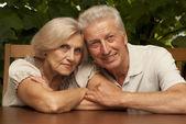 Interesting elderly couple sitting on the veranda — Stock Photo