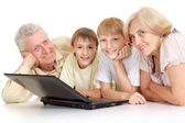 Grandchildren with their beauteous granddad and granny — Stock Photo