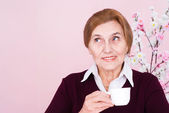 Happy old Caucasian woman sitting with a cup — Stock Photo