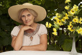 Beautiful older woman sitting on the veranda — Stock Photo