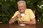 Happy older man sitting on the veranda — Foto de Stock