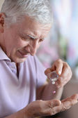 Older man taking a medicine — Stock Photo