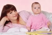 Piękne ładne matka z córką, leżąc w łóżku — Zdjęcie stockowe