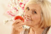 Beautiful old woman with an apple — Stock Photo