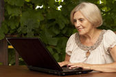 Glorious older woman sitting on the veranda — Stock Photo