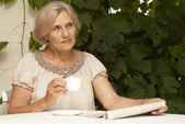 Calm older woman sitting on the veranda — Stock Photo