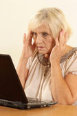 Old woman with a laptop on a beige — Stock Photo
