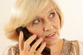 Beautiful old woman with a phone — Stock Photo
