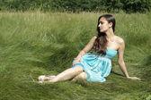 Beautiful girl sitting on the grass — Stock Photo