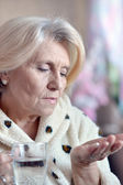 Older woman taking a medicine — Stock Photo