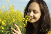Sympothetic young female in the middle of yellow flowers — Stock Photo