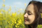 Charming young female in the middle of yellow flowers — Stock Photo