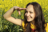 Glorious young female in the middle of yellow flowers — Stock Photo