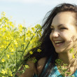 Attractive young girl in the middle  of yellow flowers — Stock Photo