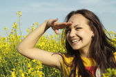 Superb young female in the middle of yellow flowers — Stock Photo