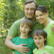 Happy family of four spends time outdoors in the summer — Stock Photo