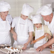 Stock Photo: Elderly couple and their grandson knead dough for pie together