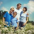 Happy family of four spends time outdoors in the summer — Stok fotoğraf