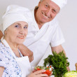 Elderly couple preparing vegetable salad together — Stok fotoğraf