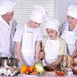 Happy grandparents and their grandchildren cook together — Stock Photo