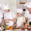 Happy grandparents and their grandchildren cook together — Stock Photo #29766505