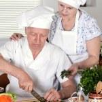 Elderly couple preparing vegetable salad together — Stock Photo