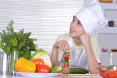 Cute boy preparing vegetarian meals in the kitchen — Stockfoto